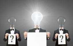 Gli uomini con le lampadine invece delle teste tengono i copyspaces Fotografia Stock