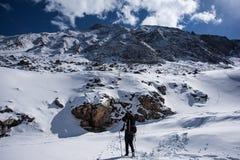 Gli uomini con lo zaino va alla cima della montagna nel giorno del sole Immagini Stock