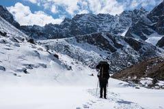 Gli uomini con lo zaino va alla cima della montagna nel giorno del sole Fotografia Stock