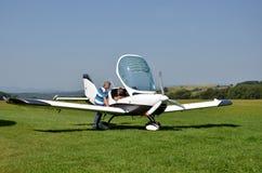 Gli uomini controllano il piccolo aeroplano personale prima del decollo e preparano per il volo accanto alla pista di atterraggio Immagine Stock