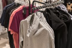 Gli uomini copre, fila della raccolta di maglia con cappuccio sul gancio del negozio Immagini Stock