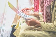 Gli uomini d'affari arabi stanno tenendo i soldi dai profitti dei Bu online immagine stock libera da diritti