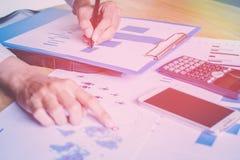 Gli uomini d'affari che parlano dei grafici e dei grafici nel posto di lavoro hanno il cellulare e calcolatori come elementi Immagine Stock Libera da Diritti