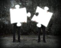 Gli uomini d'affari d'ardore di puzzle tengono per collegare il buio illuminante co Immagini Stock Libere da Diritti