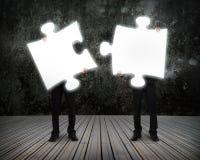 Gli uomini d'affari d'ardore di puzzle tengono per collegare il buio illuminante wo Fotografie Stock