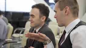 Gli uomini d'affari di tro discutono la presentazione che si siede sul confernce in ufficio luminoso archivi video