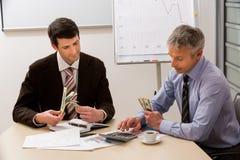 Gli uomini d'affari dividono il profitto Fotografia Stock
