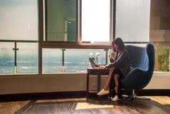 Gli uomini d'affari femminili stanno lavorando ai computer ed al caff? bevente nell'ufficio fotografie stock