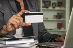 Gli uomini d'affari femminili stanno usando le carte di credito per gli acquisti online fotografia stock