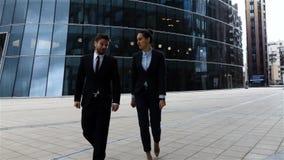 Gli uomini d'affari hanno conversazione all'aperto nel distretto aziendale video d archivio
