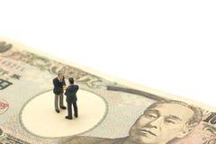 Gli uomini d'affari miniatura di 2 persone stringono le mani partecipano sulle banconote giapponesi degno 10.000 Yen facendo uso  Fotografie Stock
