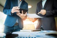 Gli uomini d'affari passa indicare al documento in touchpad durante il explan immagine stock