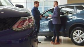 Gli uomini d'affari sta facendo un affare di acquisto dell'automobile nuova immagine stock