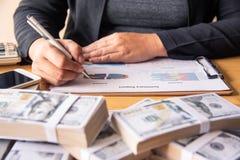 Gli uomini d'affari stanno lavorando ai dollari, calcolando i profitti e guadagnano immagine stock