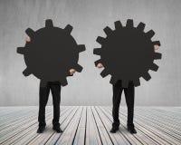 Gli uomini d'affari tengono il loro ingranaggio differente sul pavimento di legno Fotografia Stock Libera da Diritti