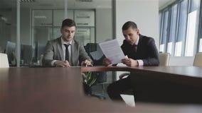 Gli uomini d'affari in vestiti ed in legami discutono un caso che si siede ad una tavola stock footage