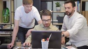 Gli uomini dei colleghe spiega i programmi di lavoro che si siedono dietro il computer portatile dentro l'ufficio video d archivio