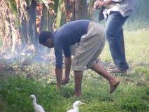 Gli uomini dell'agricoltore nell'usura tradizionale raccolgono i semi, vita rurale Fotografia Stock Libera da Diritti