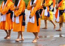 gli uomini della religione sikh con i vestiti arancio lunghi camminano a piedi nudi Fotografia Stock Libera da Diritti