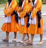 gli uomini della religione sikh con i vestiti arancio lunghi camminano a piedi nudi con Immagini Stock