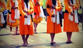 gli uomini della religione sikh con i vestiti arancio lunghi camminano a piedi nudi con Fotografia Stock Libera da Diritti