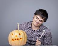 Gli uomini divertenti con la forcella provano a mangiare una zucca. Immagini Stock