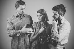 Gli uomini, donna sui fronti premurosi esamina la macchina fotografica, fondo grigio Uomini in vestiti a quadretti, retro stile a Fotografie Stock Libere da Diritti