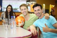 Gli uomini e la donna con le sfere si siedono alla tabella nel bowling Fotografia Stock