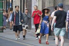 Gli uomini e la donna dei pantaloni a vita bassa si sono vestiti nello stile fresco del londinese che camminano nel vicolo del ma Immagine Stock Libera da Diritti