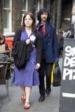 Gli uomini e la donna dei pantaloni a vita bassa si sono vestiti nello stile fresco del londinese che camminano nel vicolo del ma Fotografie Stock