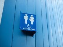 Gli uomini e la donna handicappano il segno disponibile fuori della toilette immagini stock