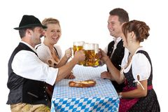 Gli uomini e le donne bavaresi tostano con lo stein della birra fotografie stock libere da diritti