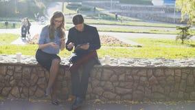 Gli uomini e le donne di affari utilizzano una compressa e un telefono nel parco video d archivio