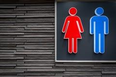 Gli uomini e le donne firma per la toilette sul fondo moderno della parete di pietra immagini stock