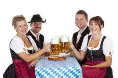 Gli uomini e le donne tostano con lo stein della birra di Oktoberfest fotografia stock libera da diritti