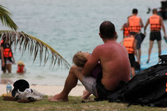Gli uomini europei prendono la cura del bambino su una spiaggia Immagine Stock Libera da Diritti
