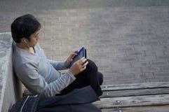 Gli uomini giapponesi sta lavorando alla sua compressa in un parco pubblico a Kobe, Giappone fotografia stock libera da diritti