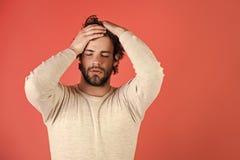 Gli uomini guarisce la cura del corpo Uomo sonnolento con la barba su fondo rosso Immagine Stock