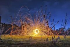 Gli uomini hanno fuso lo steelwool del fuoco del campo nel tempo dell'alba Immagine Stock