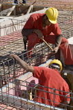 Gli uomini installa il tondo per cemento armato - verticale Immagini Stock Libere da Diritti