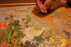Gli uomini mette un puzzle sulla tavola Ama i puzzle fotografie stock libere da diritti