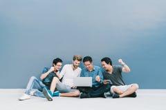 Gli uomini multietnici del gruppo 4 celebrano insieme facendo uso del computer portatile Studente di college, concetto di istruzi Immagine Stock