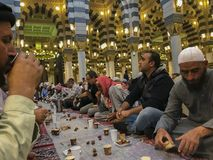 Gli uomini musulmani non identificati si rompono velocemente all'alba dentro la moschea di Nabawi in Medina, Arabia Saudita Immagine Stock