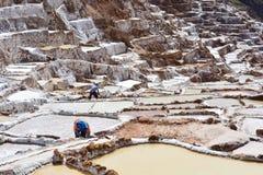 Gli uomini non identificati che lavorano al Salineras il de Mara salano i campi in Cusco, Perù Immagini Stock