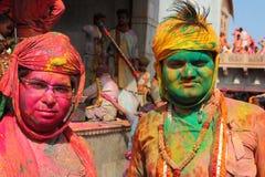 Gli uomini non identificati con il fronte spalmato di colori partecipano alla celebrazione variopinta di Holi al tempio di Krishn fotografia stock libera da diritti