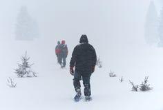 Gli uomini passa attraverso la bufera di neve sugli snowshoes Immagine Stock