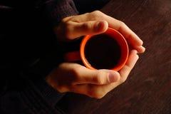Gli uomini passa la tenuta della tazza arancio con la vista superiore del caffè nero o del tè nero sulla tavola di legno marrone  Immagini Stock