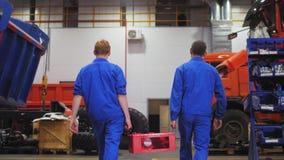 Gli uomini portano la batteria di accumulatori nella parte del movimento lento del negozio video d archivio
