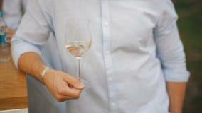 Gli uomini scuote il vino bianco in un bicchiere di vino trasparente Un uomo che assaggia un vetro di vino bianco stock footage