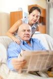 Gli uomini senior sorridenti con il giornale e maturano le donne Fotografia Stock